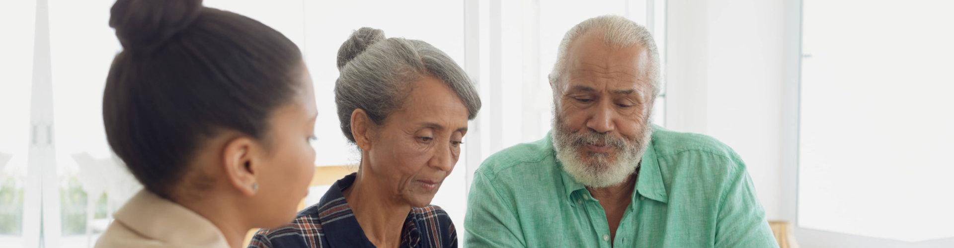 caregiver talking to a senior couple