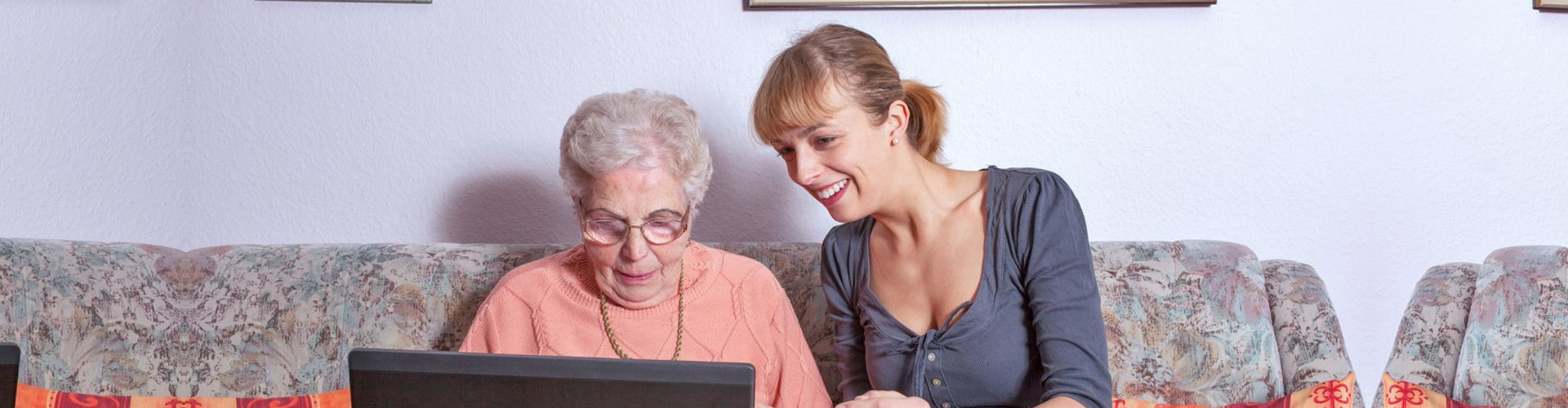 caregiver teaching senior woman to use a laptop